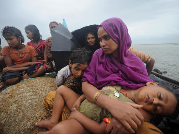 Rohingya Muslims, trying to cross the Naf river into Bangladesh to escape sectarian violence in Myanmar, look on from an intercepted boat in Teknaf on July 13, 2012.