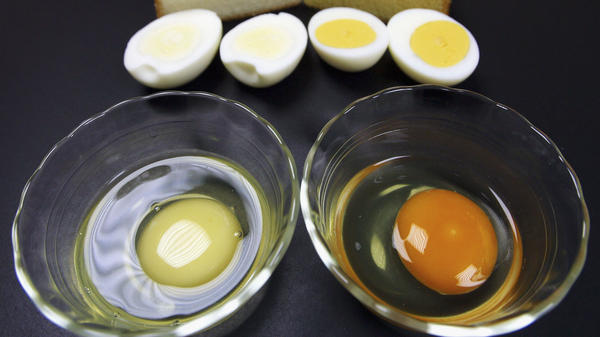The white egg yolk at left, seen next to a yellow yolk, may seem strange, but it's just a result of the chicken feed used, scientists say.