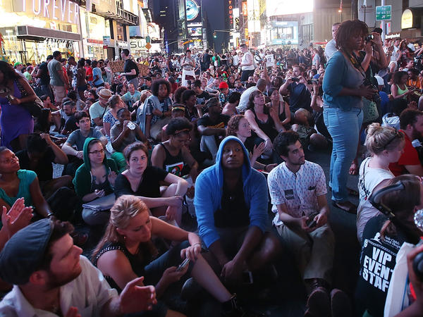 Trayvon Martin supporters sit in New York City's Times Square on Sunday after marching from a rally for Martin in Manhattan.
