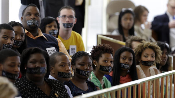 Opponents of North Carolina's new voter ID legislation wear tape over their mouths while sitting in the gallery of the House chamber of the North Carolina General Assembly in Raleigh, N.C., on April 24, where lawmakers debated new voter laws. On Monday, Gov. Pat McCrory signed a new law that requires a state-approved photo ID to vote and cuts early-voting opportunities.