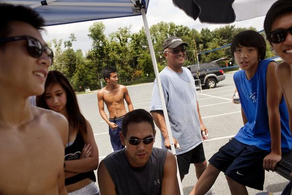 "Jeff Yuen, 53 (center), a financial controller for a government contractor, coaches younger 9-man players. ""We got involved because our dads would do this every Sunday,"" he says. ""But once they left the cities to move to the suburbs, the Asian community started losing their roots. So we are trying to maintain our rich heritage."""