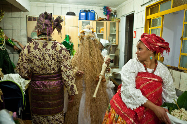 Woman prepare food for orixas in the kitchen of the CandombléŽ temple. The priest and the people dressed as the spirits pass through to enter the main room for the ceremony.