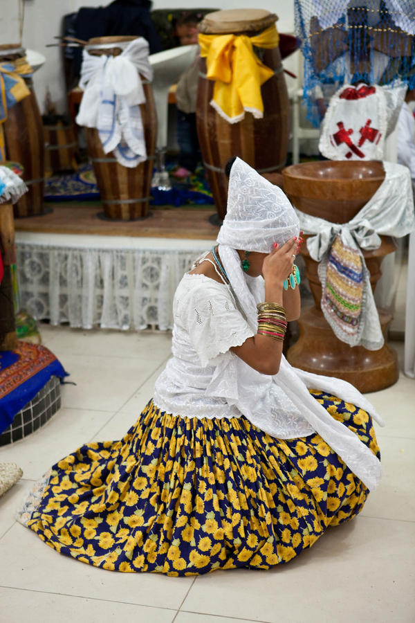 """A woman fixes her turban while practitioners perform """"cleaning dancing"""" before the manifestation of the orixas."""
