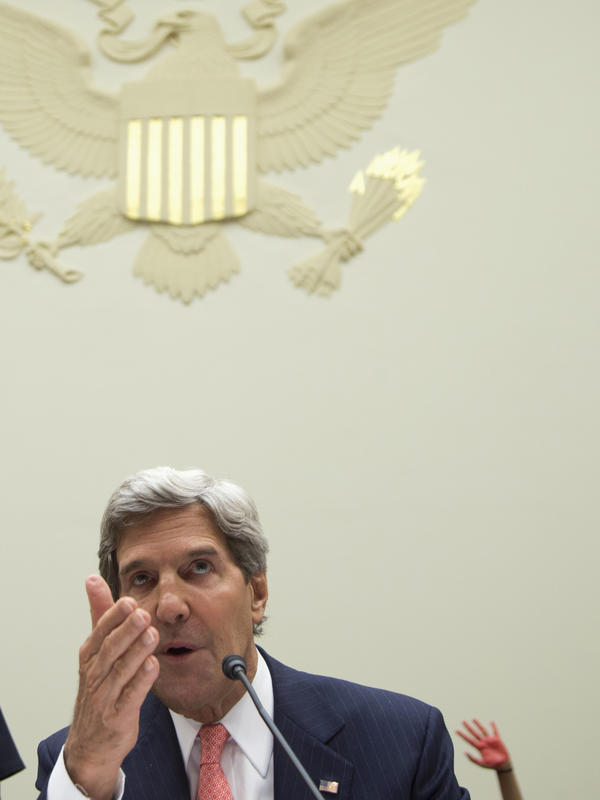A Code Pink protester holds up a red-painted hand behind Secretary of State John Kerry as he testifies on Capitol Hill on Sept. 4 about possible military strikes on Syria.