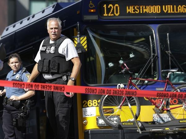 Police officials stand next to a bullet-ridden Seattle Metro bus on Aug. 12. A man with a history of mental illness shot and wounded the driver, then died in a chaotic shootout with police.