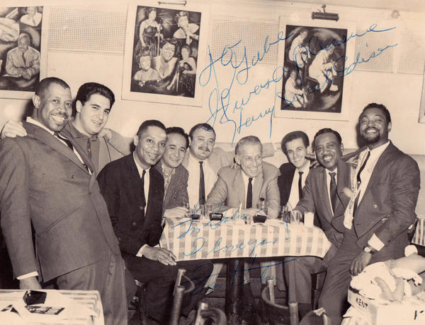 """Gabe Baltazar (fourth from left) at New York City's Birdland Club in 1962, with members of Stan Kenton's band and the Count Basie Orchestra. The photo, from Baltazar's collection, is signed by Kenton (fourth from from right) and trumpeter Harry """"Sweets"""" Edison (second from right)."""