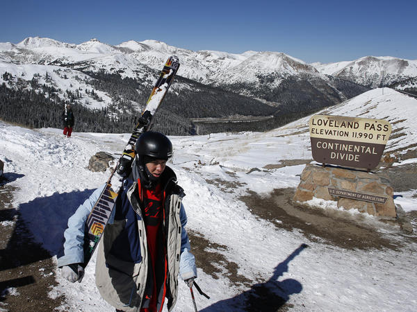 Weeks before the opening of Colorado ski areas, a skier hikes up to the top of the Continental Divide, elevation 11,990 feet, a day after fresh snow covered the mountain peaks around Loveland Pass, Colo., Saturday.