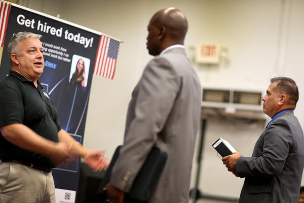 Hans Kahl (left) speaks with prospective employees at a job fair for veterans, in Miami on Tuesday. With job growth still slow, the Federal Reserve may keep trying to stimulate the economy.