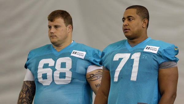 "Miami Dolphins guard Richie Incognito (left) and tackle Jonathan Martin stand on the field during practice in Davie, Fla. Martin left the NFL after he faced harassment from Incognito that his lawyer said went ""beyond locker-room hazing."""