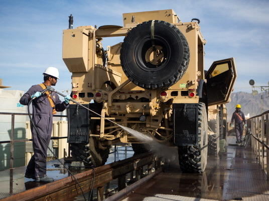 A civilian contractor power washes a mine-resistant, armored-protective vehicle at Bagram Air Field, Afghanistan, in May.