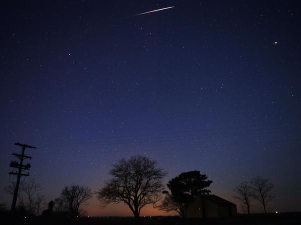 A Geminid meteor streaks across the sky early Friday near Scotland, Md.