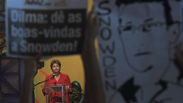 Brazil's President Dilma Rousseff speaks in Sao Paulo on Dec. 19, framed by posters held by protesters calling for asylum for National Security Agency leaker Edward Snowden.