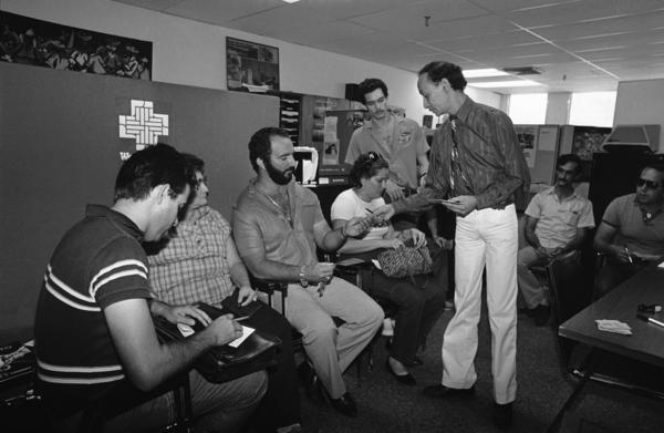 Cuban immigrants are handed forms to fill out by an immigration and naturalization official in Miami on Dec. 3, 1984, so they can become permanent residents of the United States.