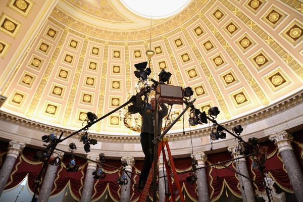 Television lighting technicians build sets inside Statuary Hall for post-speech interviews.