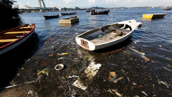 Boats float along the shoreline of the polluted waters of Guanabara Bay on Jan. 21 in Rio. The bay will be the site of sailing events during the Olympics. Local residents recently protested the high level of pollution.