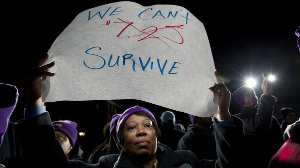 Darlene Handy of Baltimore holds up a banner at a rally supporting a pay measure in Maryland. More than 20 states have raised minimum pay rates above the federal level.