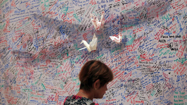 A woman reads messages for passengers aboard a missing Malaysia Airlines plane at a shopping mall in Kuala Lumpur, Malaysia on Saturday.