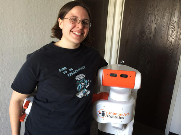 Melonee Wise the CEO and co-founder of Unbounded Robotics. She is standing with the company's robot, the UBR-1.