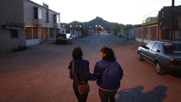 Yvonne Navarro walks through her Juarez neighborhood with her daughter, also named Yvonne, who at 16 is the same age her mother was when her mother went to work in <em>maquiladoras</em>.