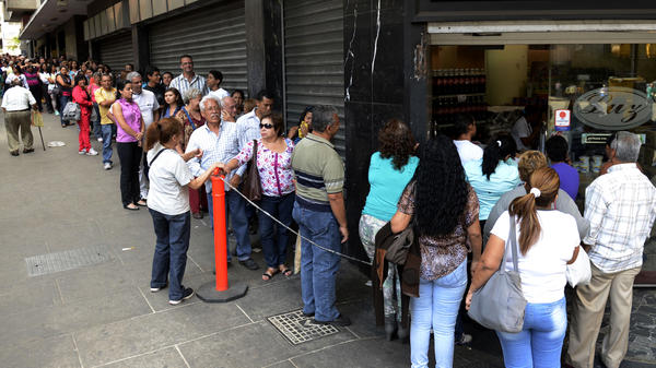 Venezuelans line up to buy goods at a store in Caracas on March 10. Protesters have been taking to the streets for weeks over the country's troubled economy and other issues. The government introduced a new foreign currency exchange system on Monday, seeking to stabilize the bolivar, which has lost much of its value against the U.S. dollar.