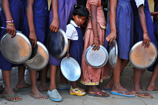 Indian schoolchildren wait in line for food at a government primary school in Hyderabad, India. Consistent access to nutritious food and clean water is key to helping children thrive, researchers say.
