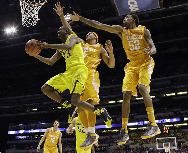 Michigan's Caris LeVert (left) gets a shot past Tennessee's Jarnell Stokes (No. 5) and Jordan McRae (No. 52) in Friday night's NCAA Midwest Regional semifinal. Michigan advanced despite being outscored in the second half.