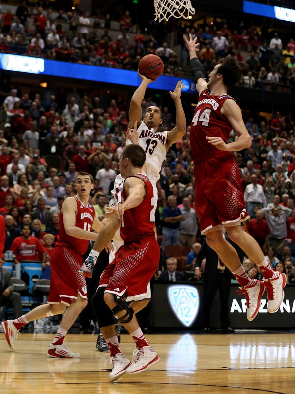 Nick Johnson of the Arizona Wildcats is called for an offense foul as he drives on Josh Gasser, No. 21 of the Wisconsin Badgers, in overtime during the West Regional Final of the 2014 NCAA Men's Basketball Tournament. Arizona's fans rioted after the close loss.