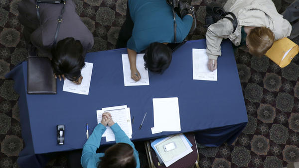 Job seekers sign in before meeting prospective employers during a January career fair at a hotel in Dallas.