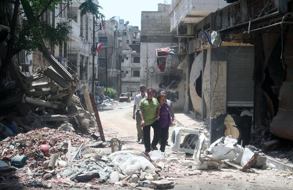 Residents of Homs return to survey the damage to their city on May 27. Three weeks earlier, rebels withdrew under a truce, and government forces retook control. Homs was considered the birthplace of the uprising against Assad, and retaking it was considered an important victory for the government.