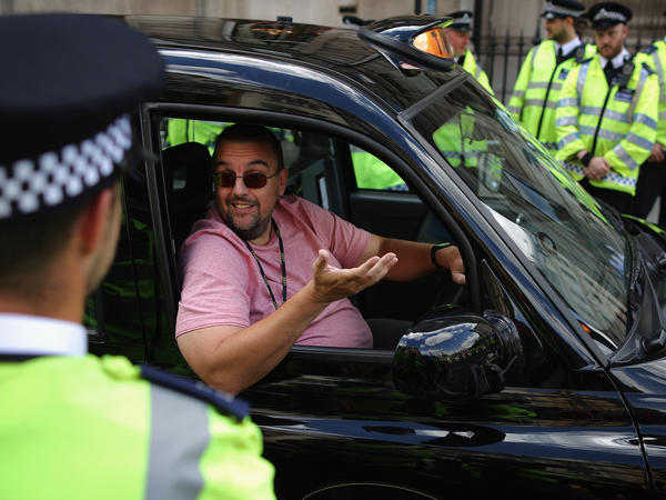 A London taxi driver speaks with police officers during a protest against Uber on Wednesday.