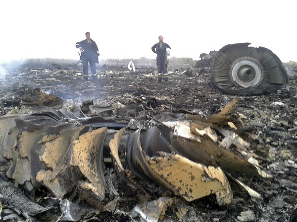 Ukrainian emergency workers are seen Thursday at what's reported to be the crash site of a Malaysia Airlines Boeing 777 in the settlement of Grabovo, in the Donetsk region.