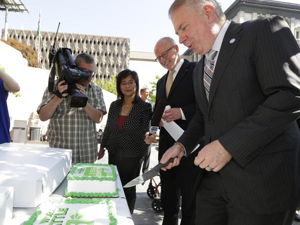 Seattle Mayor Ed Murray (right) and Seattle City Council President Tim Burgess cut a cake to celebrate city's raised minimum wage.