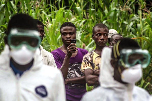 <p>Villagers watch a Red Cross burial team carry out a neighbor who may have died of Ebola in the village of Pendembu, Sierra Leone. The goal is to prevent transmission of the virus from the body of the deceased.</p><p></p>