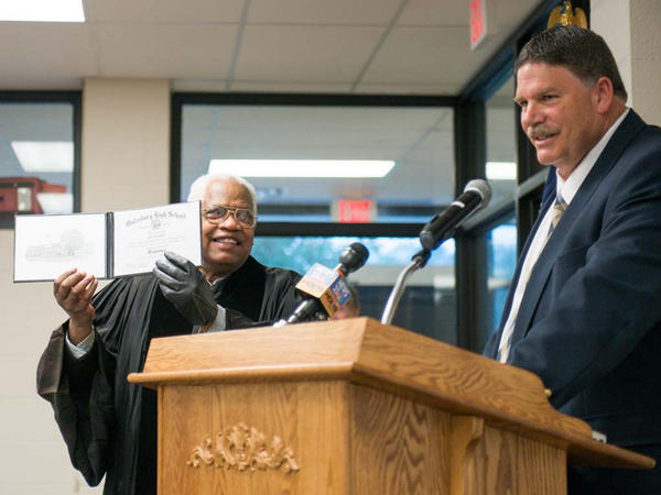 Alva Earley shows off his diploma after receiving it from Galesburg Superintendent Bart Arthur.