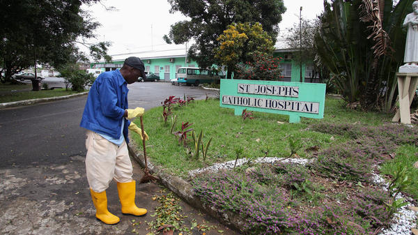 Wearing protective boots and gloves, a nurse sweeps the grounds of St. Joseph's Catholic Hospital. Overwhelmed by Ebola, the facility is now closed.