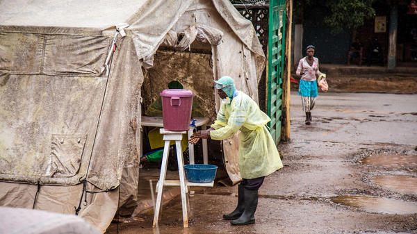 A health worker cleans his hands with chlorinated water before entering an Ebola screening tent at the Kenema Government Hospital in Sierra Leone. More than 300 Sierra Leoneans have died of the disease.