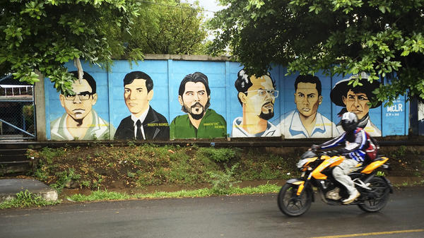 A motorcyclist drives past a mural of revolutionary heroes in Managua, Nicaragua. Most streets in the country don't have names. People give directions by using reference points, mostly Lake Managua, when in the capital.