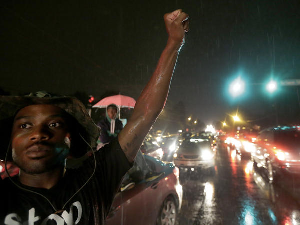 A protester holds up a clenched fist in front of a convenience store that was looted and burned following the shooting death of Michael Brown by police nearly a week ago in Ferguson, Mo.