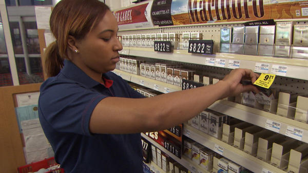 An unnamed CVS employee removes tobacco products from the store shelves in East Greenwich, R.I.