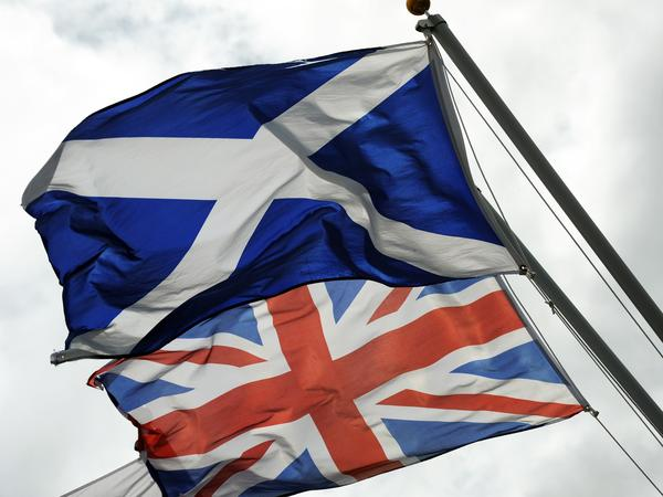 The Saltire, the flag of Scotland, flies near the Union Jack in Gretna in Scotland. Some economists say Thursday's vote on Scotland's independence could have wide-ranging economic impacts.