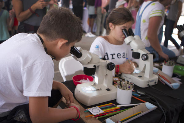Young makers peer through microscopes to make tiny, tiny drawings, thanks to the Learning Technologies Center at the Minnesota Science Museum.