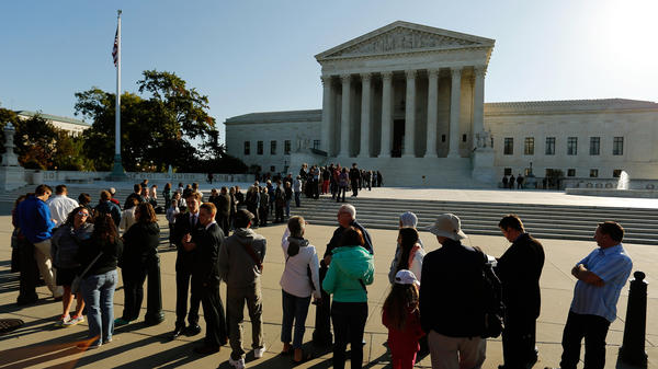 Visitors stand in line to watch arguments on the first day of the new term of the U.S. Supreme Court in Washington on Monday. On Tuesday, the court will take up the case of Gregory Holt, who argues that Arkansas prisoners like himself should be allowed to wear short beards.