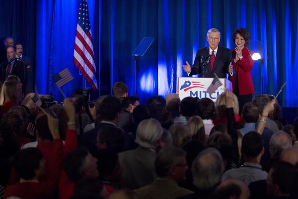 Sen. Mitch McConnell is accompanied by his wife, Elaine Chao, at his victory event Tuesday in Louisville, Ky.