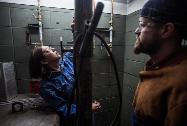 Spartanburg Community College welding instructor Teresa Elder (left) grades Harris during class.