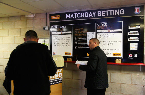 This is a photo of football fans look at the match day betting odds prior to the Barclays Premier League match between Stoke City and Hull City at Britannia Stadium on March 29, 2014 in Stoke on Trent, England.  (Paul Thomas/Getty Images)