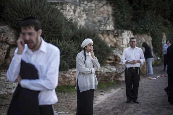 People react as they stand outside a synagogue on Tuesday in Jerusalem, Israel. Four Israelis were killed and several others wounded in a terrorist attack at the synagogue.