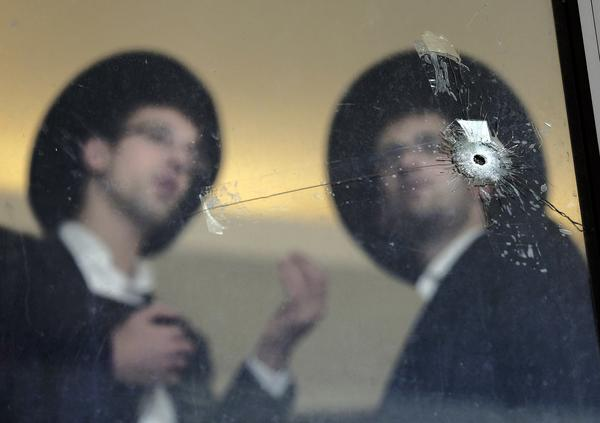 Ultra Orthodox Jews look at bullet holes in the main window of a synagogue in Jerusalem on Wednesday.