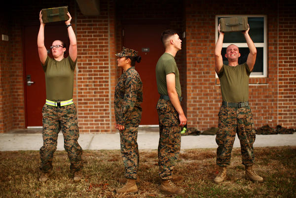 Katie Gorz (left) performs the ammo can lift next to male Marines as they go through the combat fitness test. The Marine Corps is experimenting with inserting some women into combat infantry roles that have historically been limited to men. At Camp Lejeune, female Marines are undergoing the same training as their male counterparts for combat arms.
