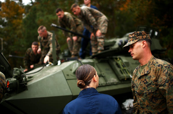 Lance Cpl. Julia Carroll chats with another service member during light armored vehicle training at Camp Lejeune. She is one of 14 women who made it out of a basic infantry training course and on to Lejeune.