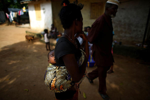 Sidulamin Sisay, 1, rides on his mother's back. She is the aunt of a small boy and girl who were taken away to be treated for Ebola at the children's hospital in Freetown Sierra Leone. Nine members of their immediate family died from the disease. The two young children were sick and could only be cared for at arm's length.